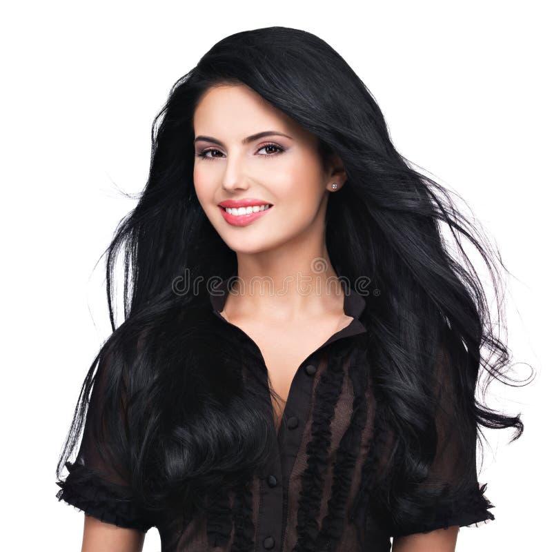 Портрет молодой усмехаясь женщины с длинными коричневыми волосами стоковое фото