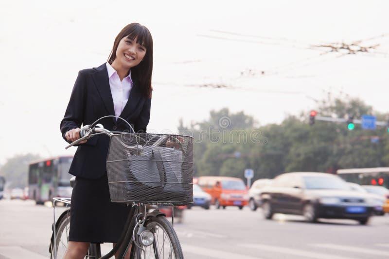 Портрет молодой усмехаясь коммерсантки ехать велосипед на улице в Пекине, смотря камеру стоковое фото