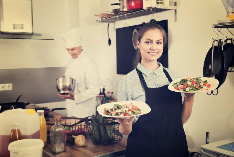 Портрет молодой усмехаясь рисбермы официантки женщины нося стоковые изображения rf