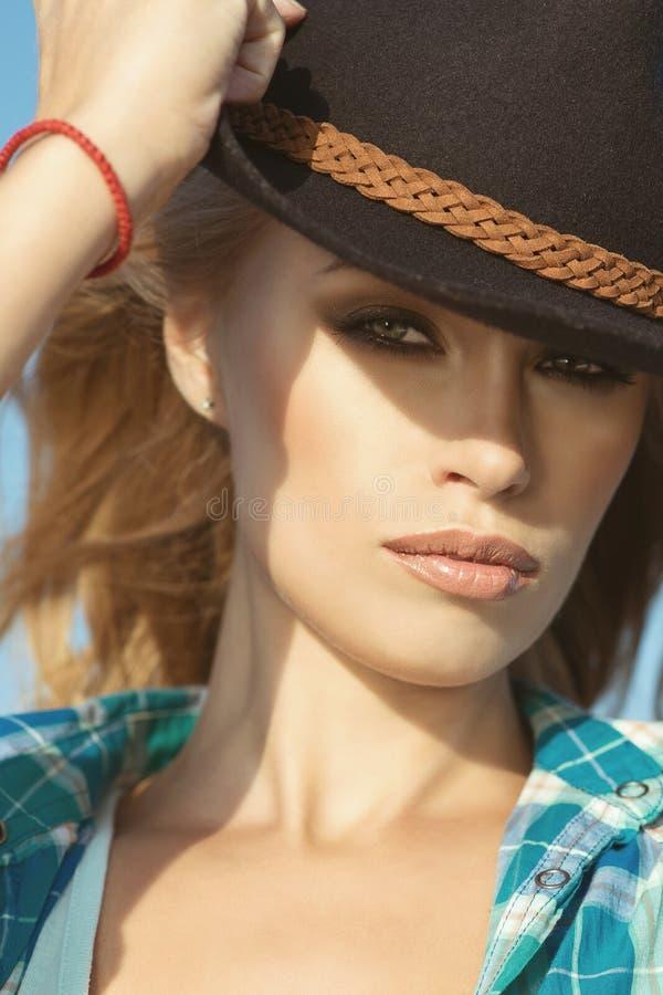 Портрет молодой шикарной белокурой женщины при провокационный состав нося черную фетровую шляпу стоковая фотография rf