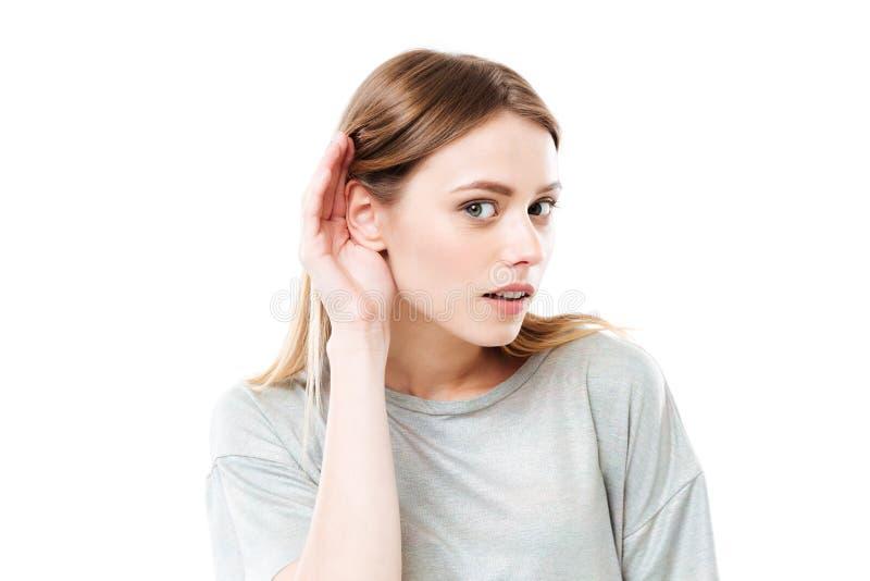 Портрет молодой любознательной девушки пробуя услышать слухи стоковое фото