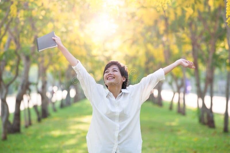 Портрет молодых азиатских женщины и книги в руке руки поднимая как VI стоковое фото rf