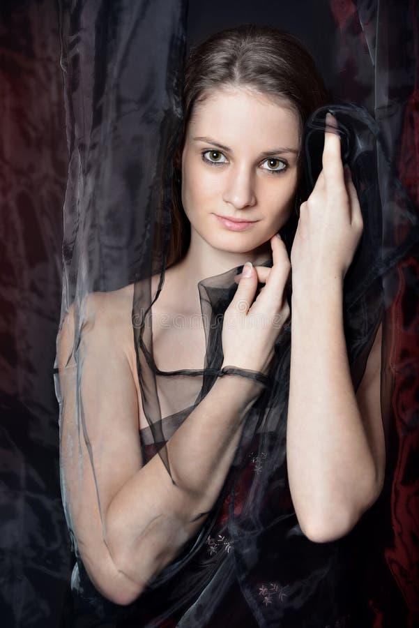 Портрет молодых женщин hiden в занавесах стоковые изображения rf