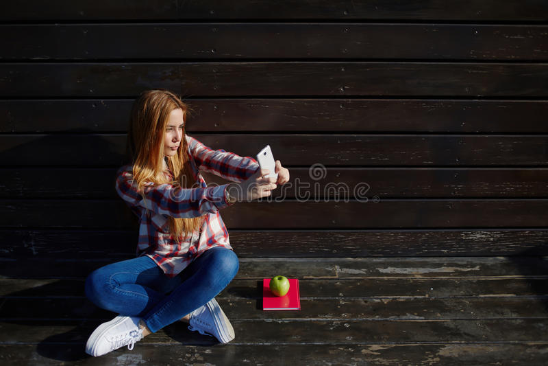 Портрет молодых милых женщин фотографируя для социального изображения сети пока отдыхающ outdoors стоковые изображения