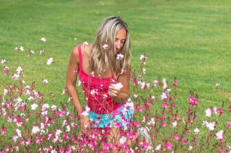 Портрет моды девушки белокурых волос привлекательных детенышей усмехаясь красивый курчавый тонкий в розовой футболке представляя  стоковая фотография rf