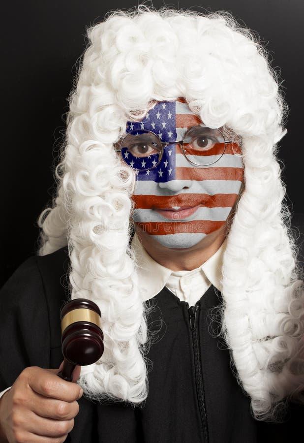 Портрет мужского американского юриста с покрашенным молотком судьи удерживания флага США стоковые изображения