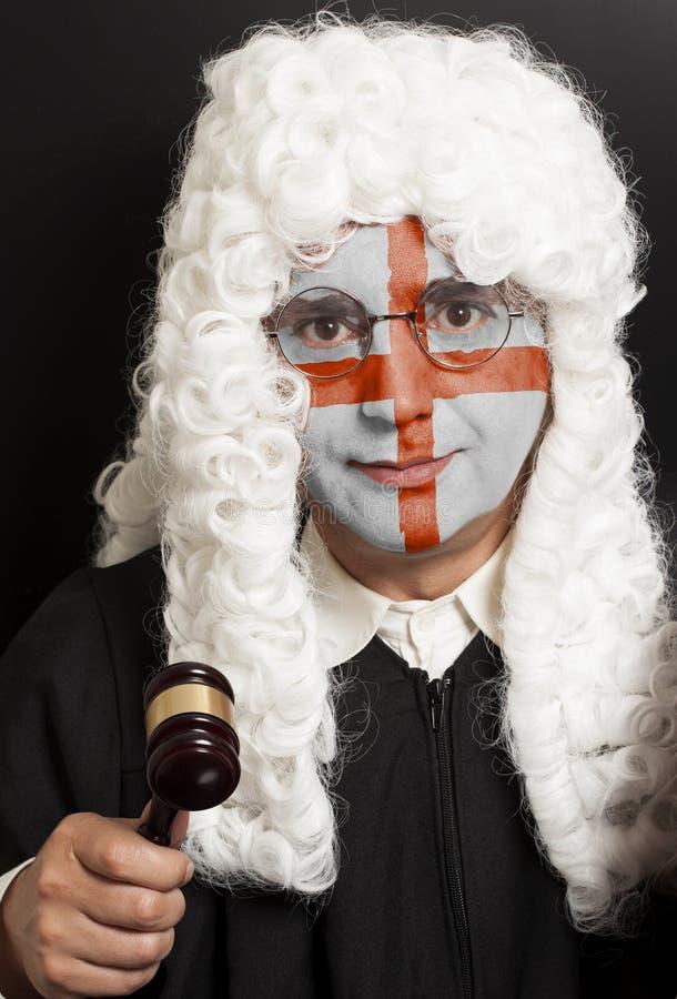 Портрет мужского английского юриста с покрашенным молотком судьи удерживания флага английского языка стоковые изображения