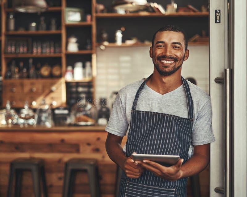 Портрет мужского владельца держа цифровой планшет в его кафе стоковые фото