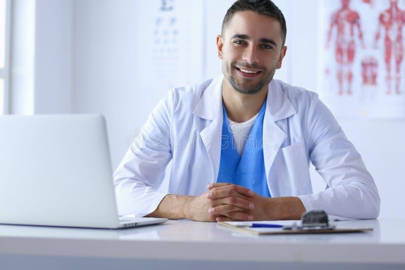 Портрет мужского доктора при компьтер-книжка сидя на столе в медицинском офисе стоковое фото rf