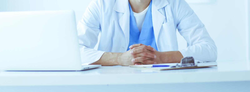 Портрет мужского доктора с ноутбуком сидя на столе в медицинском офисе стоковые фотографии rf