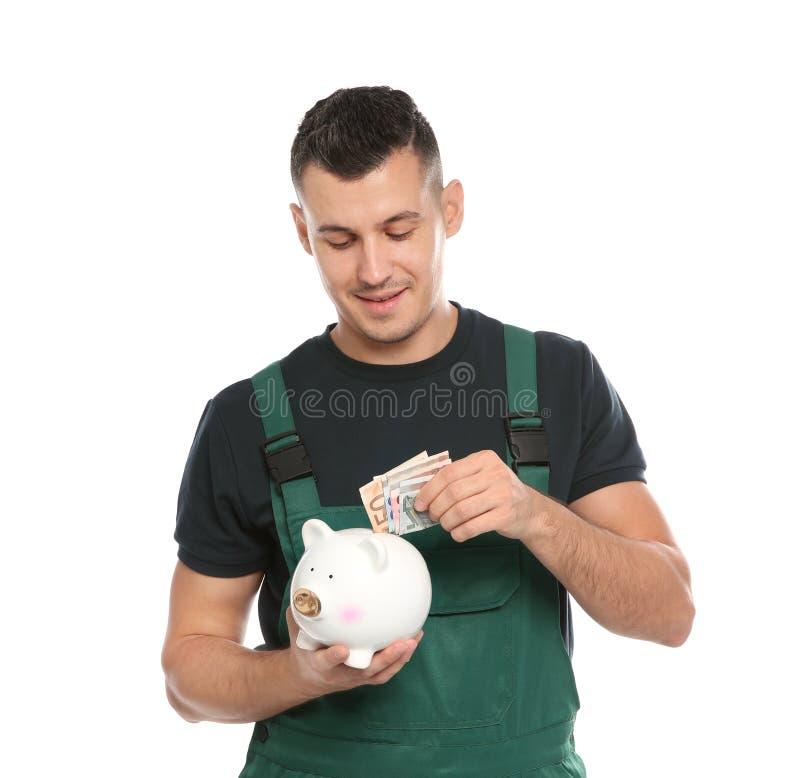 Портрет мужского работника в форме кладя деньги стоковые фото