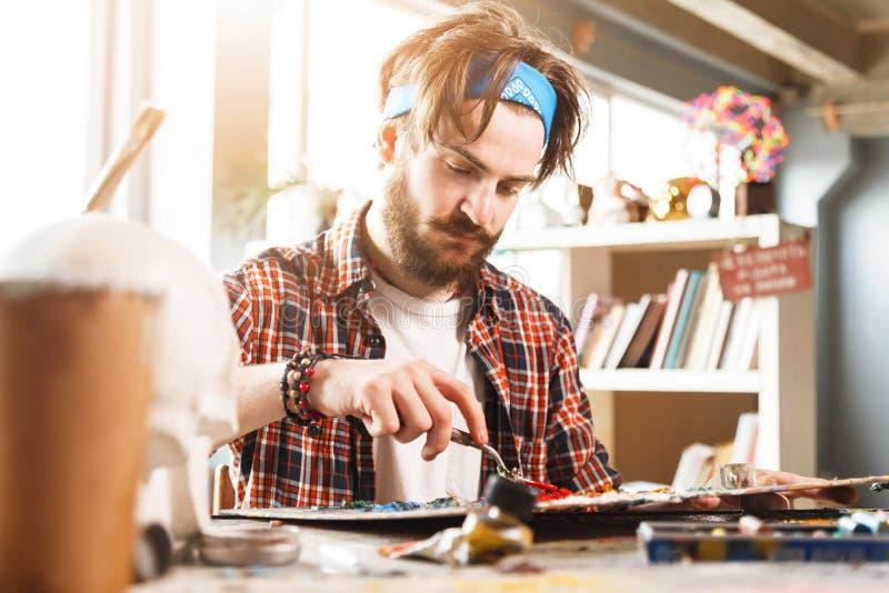 Портрет мужского художника работая на картине в студии стоковое фото