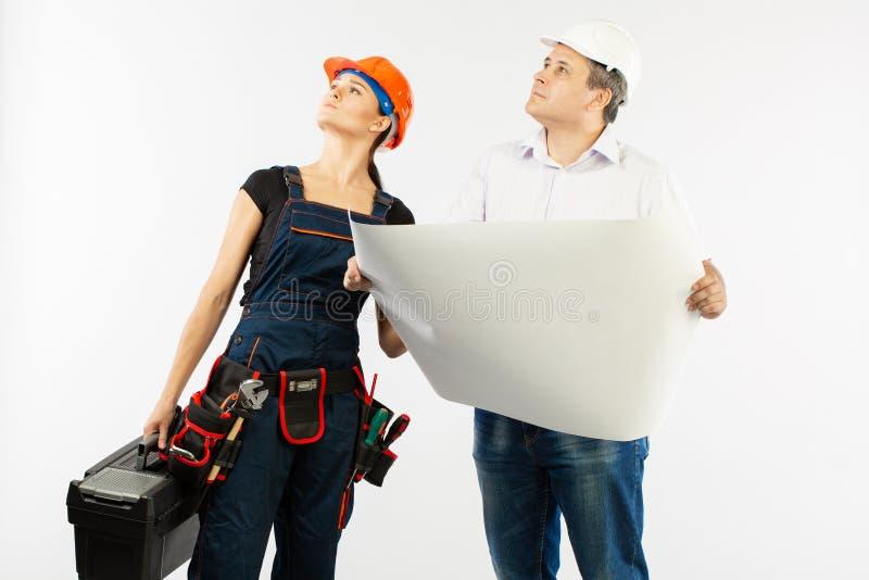 Портрет мужской женщины архитектора и построителя обсуждая строящ план мастер держа бумагу крена стоковое изображение