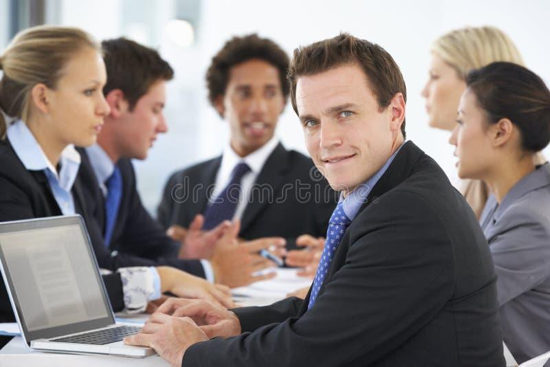 Портрет мужской исполнительной власти с встречей офиса в предпосылке стоковое фото