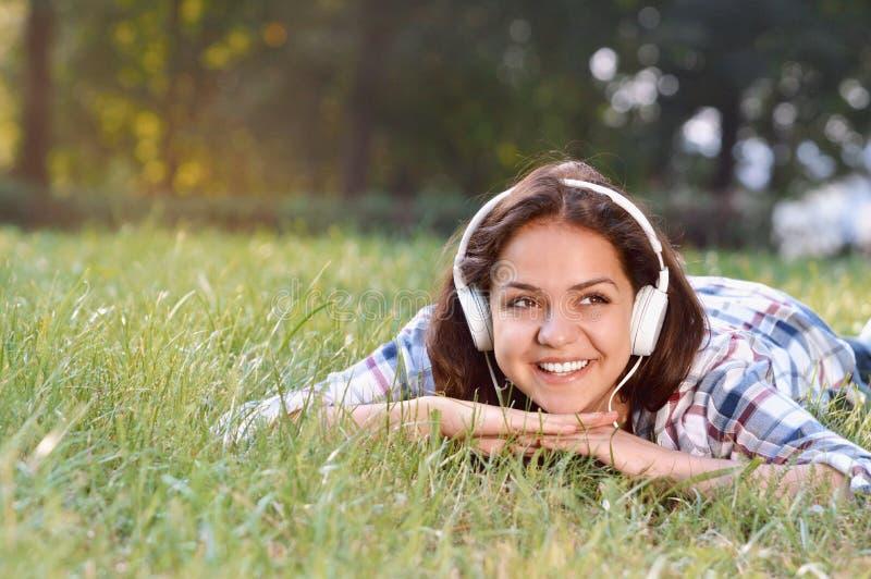 Портрет музыки маленькой девочки слушая лежа на траве стоковое фото
