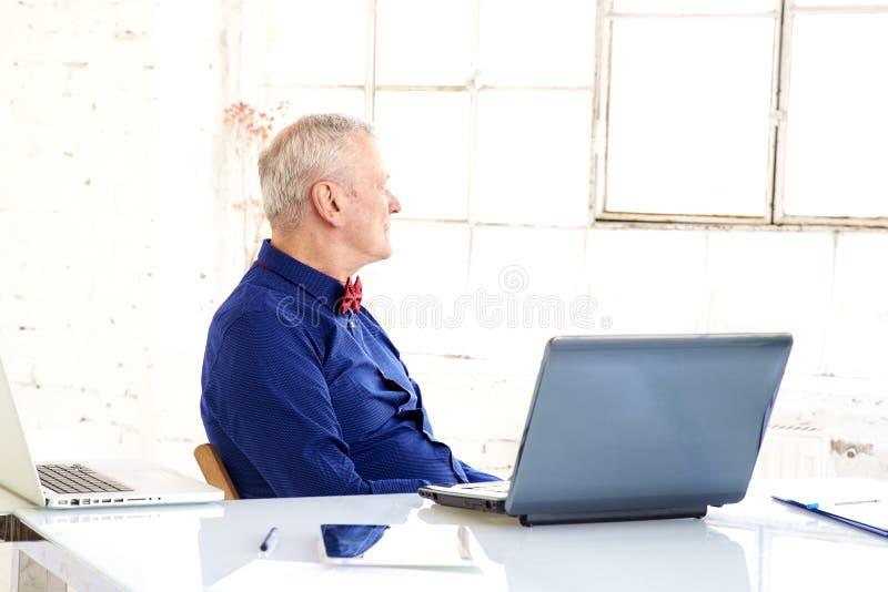 Портрет мысли старшего бизнесмена сидя в офисе за его ноутбуком стоковая фотография