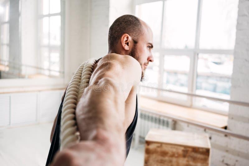 Портрет мышечного мужского спортсмена делая тренировки с веревочкой сражения на спортзале crossfit стоковое изображение