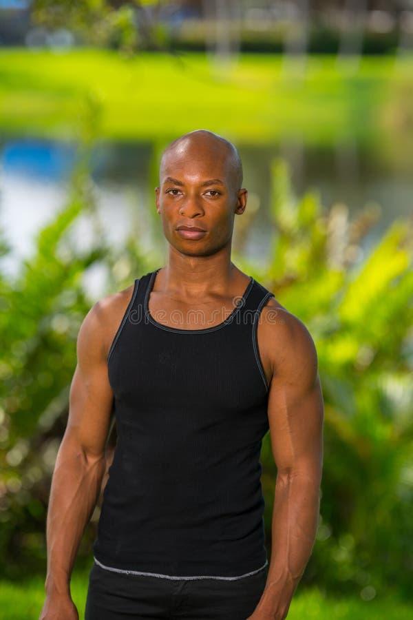Портрет мышечной модели фитнеса представляя в парке стоковая фотография