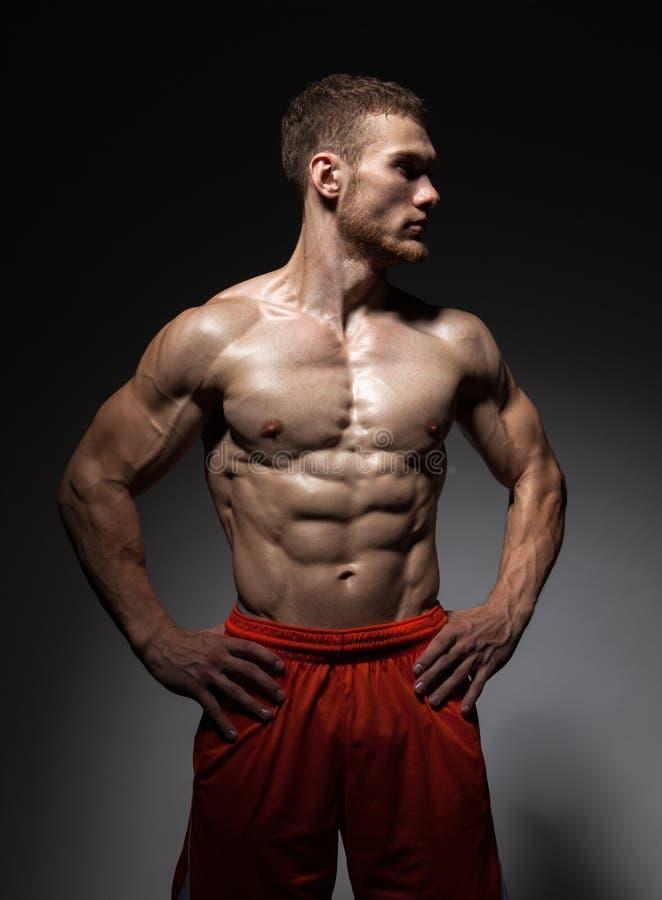 Портрет мышечной мужской модели против черной предпосылки стоковое изображение