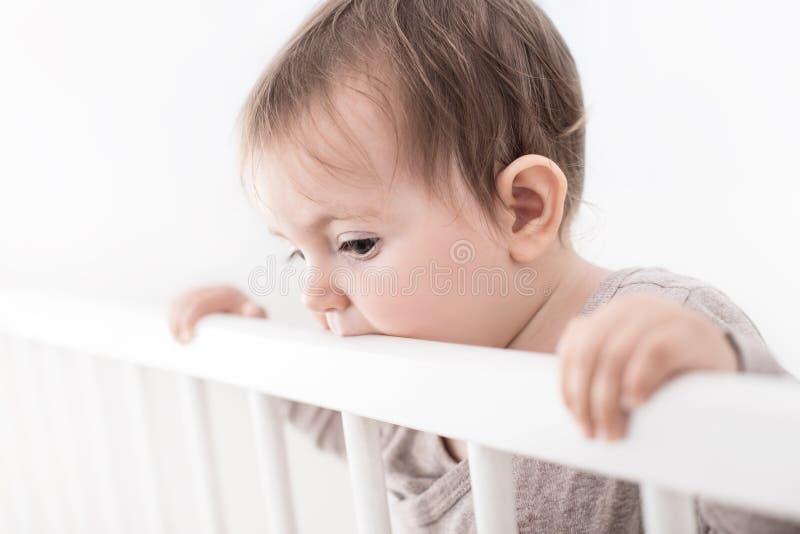 Портрет младенца лечения в его кроватке, изолированный на белизне стоковые изображения
