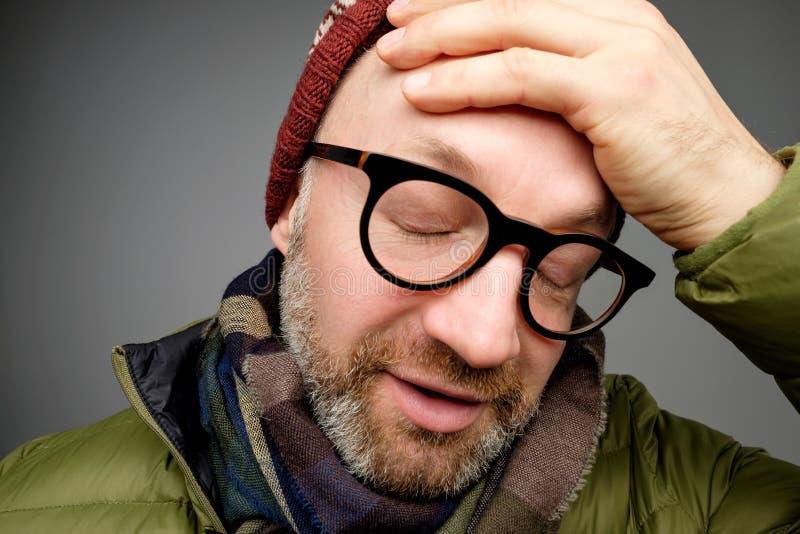 Портрет надоеданного утомленного красивого человека с щетинкой, полагаясь стороной в наличии и смотрящ равнодушный спуск стоковое изображение