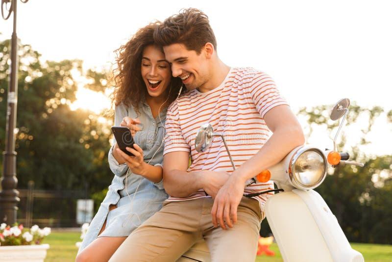 Портрет наушников человека и женщины нося слушая музыку пока сидящ на мотоцикле совместно на улице города стоковые изображения