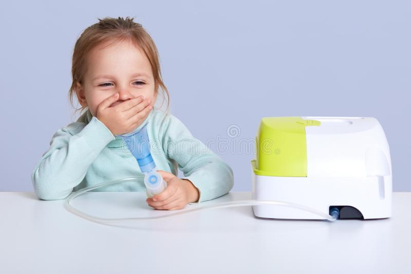 Портрет небольшой девушки делая вдыхание, сидя на таблице, носит в свете - голубой свитер шеи turle, имеет проблему со здоровым, стоковые изображения