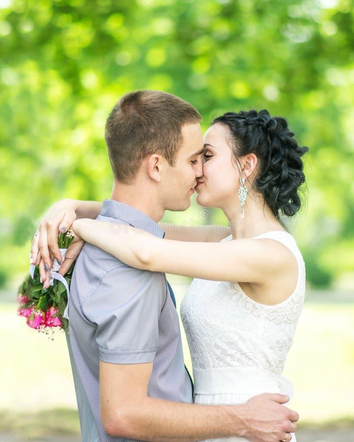 Портрет невесты красивых молодых пар женской с малым пинком свадьбы цветет букет роз и жених мужчины целуя в summe стоковые изображения rf