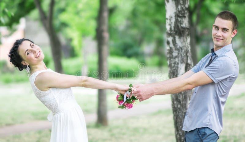 Портрет невесты счастливых красивых молодых пар женской с малой свадьбой цветет букет роз и жених мужчины держа руки, стоковое изображение rf