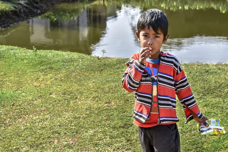 Портрет невиновного бедного мальчика положения Индии на стороне прудов и смотреть камеру, нося традиционное платье стоковое фото rf