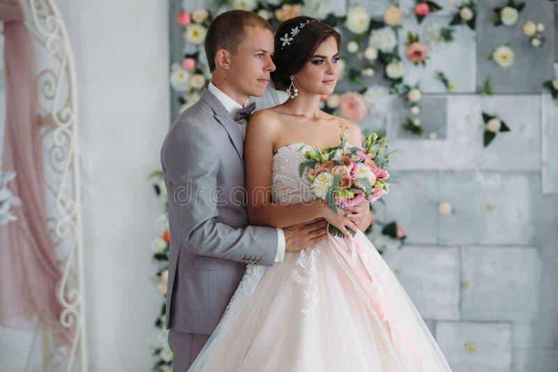 Портрет новобрачных на день свадьбы Groom в сером костюме с белой рубашкой и бабочкой обнимает красивую невесту стоковая фотография rf