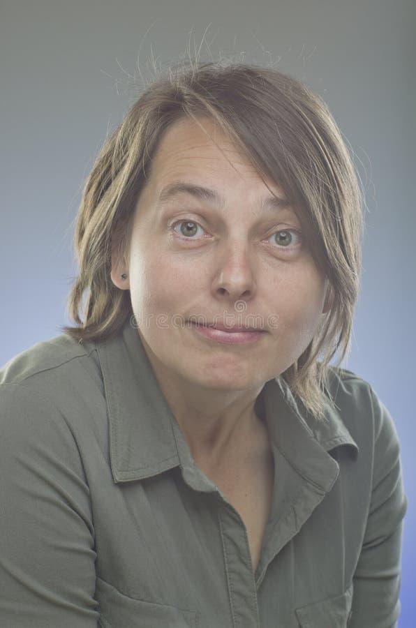 Портрет нормальной девушки смотря удивленный Красивый портрет женщины над серой предпосылкой стоковое фото rf