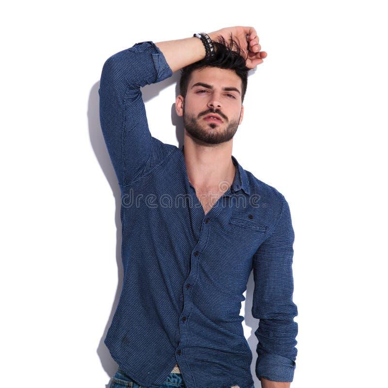Портрет обольстительного молодого человека с рукой на голове стоковые изображения