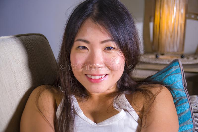Портрет образа жизни близкий поднимающий вверх молодой красивой и счастливой азиатской китайской женщины лежа дома кресло софы пр стоковая фотография