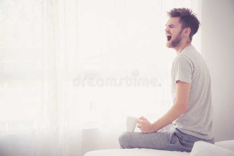 Портрет образа жизни концепции спальни: Человек держа чашку кофе и зевок стоковая фотография rf