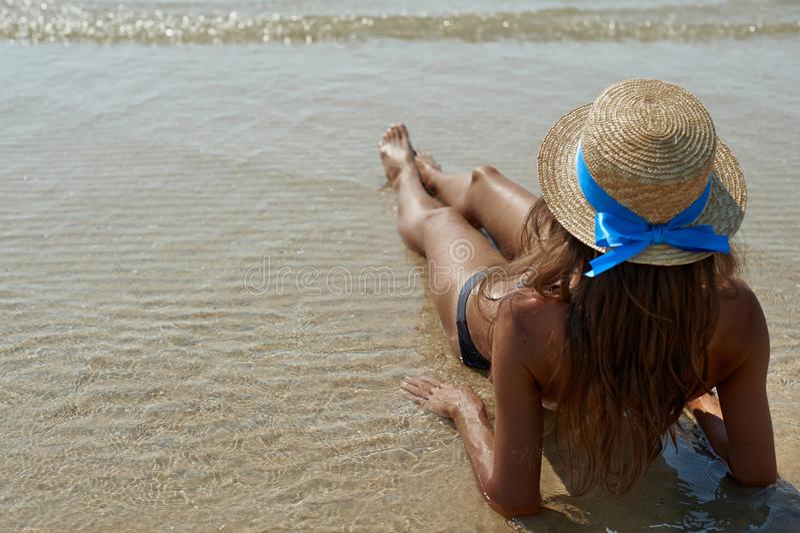 Портрет образа жизни лета довольно детенышей suntanned женщина в шляпе Наслаждаться жизнью и сидеть на пляже, время к стоковые фотографии rf