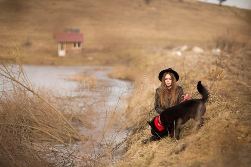 Портрет образа жизни молодой женщины в черной шляпе с ее собакой, отдыхая озером на славный и теплый день осени стоковое изображение rf