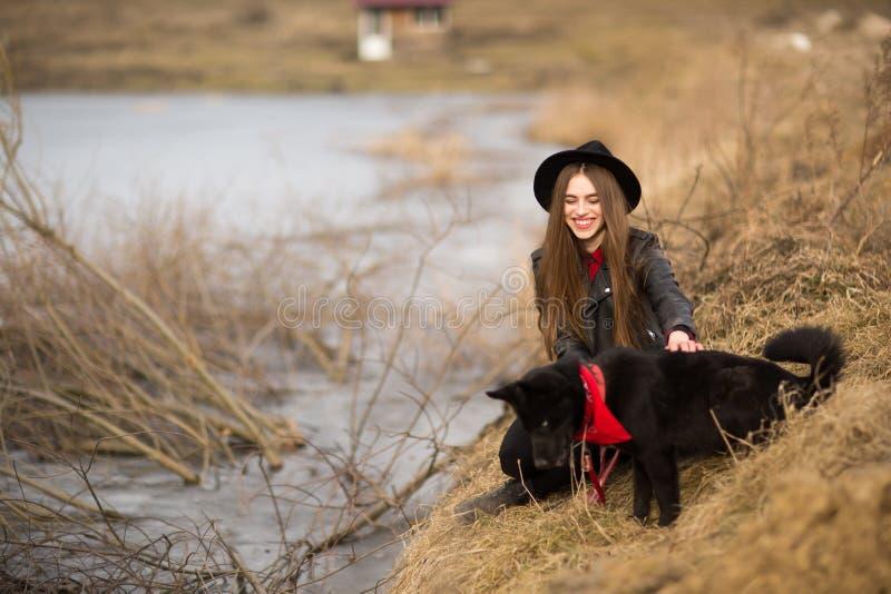 Портрет образа жизни молодой женщины в черной шляпе с ее собакой, отдыхая озером на славный и теплый день осени стоковая фотография rf