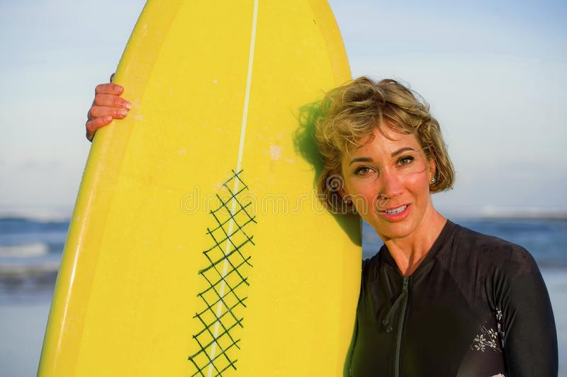 Портрет образа жизни молодой сексуальной красивой и счастливой женщины серфера держа желтое holid лета доски прибоя усмехаясь жиз стоковые фотографии rf