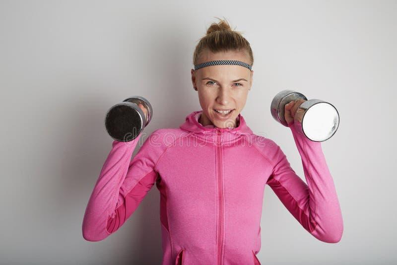 Портрет образа жизни молодой женщины фитнеса милой нося розовые спорт одевает Девушка спорта используя запонки для манжет стоковая фотография