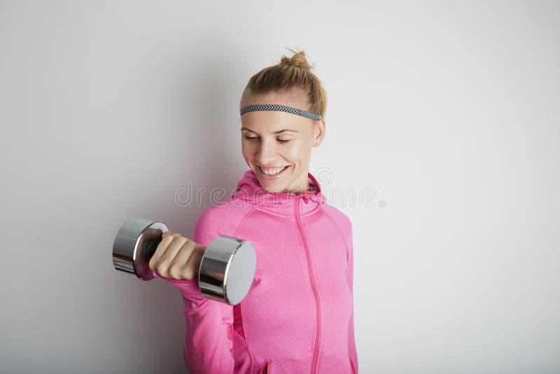 Портрет образа жизни молодой женщины фитнеса милой нося розовые спорт одевает Девушка спорта используя запонки для манжет стоковые изображения