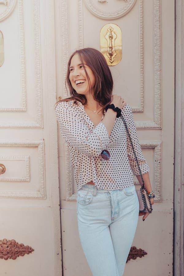Портрет образа жизни на открытом воздухе лета усмехаясь милой молодой женщины близко к старой двери имея потеху в городе Мадрида, стоковые изображения