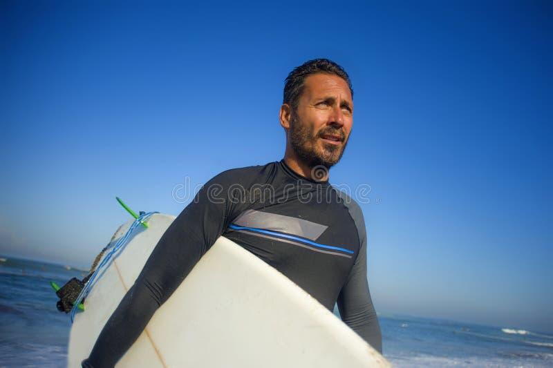 Портрет образа жизни привлекательного и крутого человека 3os серфера к 40s в купальнике неопрена занимаясь серфингом представляя  стоковые фото