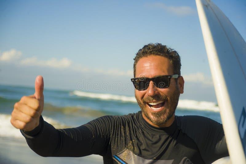 Портрет образа жизни привлекательного и счастливого человека 3os серфера к 40s в купальнике неопрена занимаясь серфингом представ стоковые фото