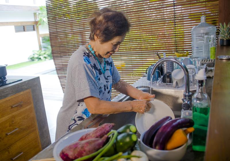 портрет образа жизни старшего счастливого и сладостного азиатского японца выбыл, женщина варя дома кухню моя блюда стоковые фото