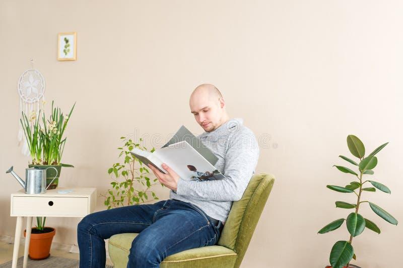 Портрет облыселого человека читая большую книгу пока сидящ в кресле детеныши домашнего человека ослабляя стоковое фото rf