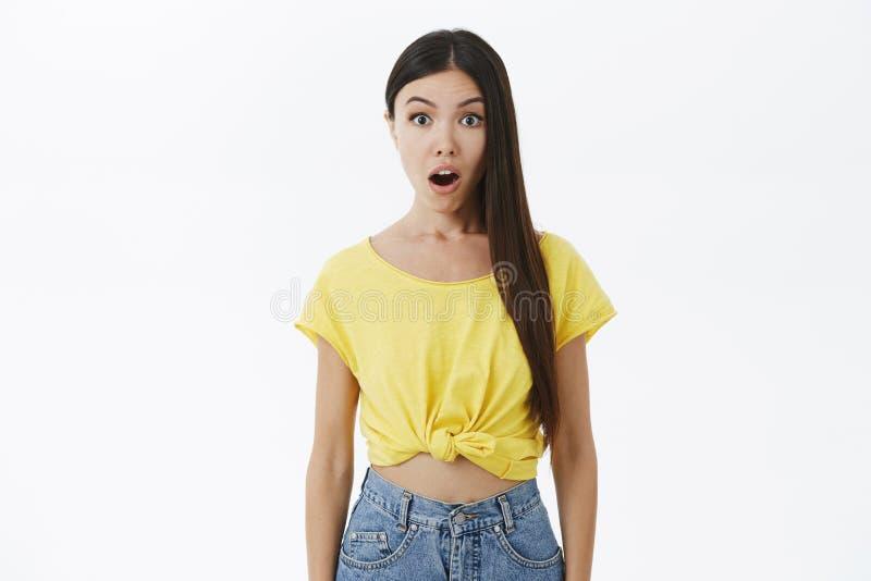 Портрет оглушенной и изумленной привлекательной европейской женщины в челюсти желтой стильной футболки падая от удивленный и стоковая фотография
