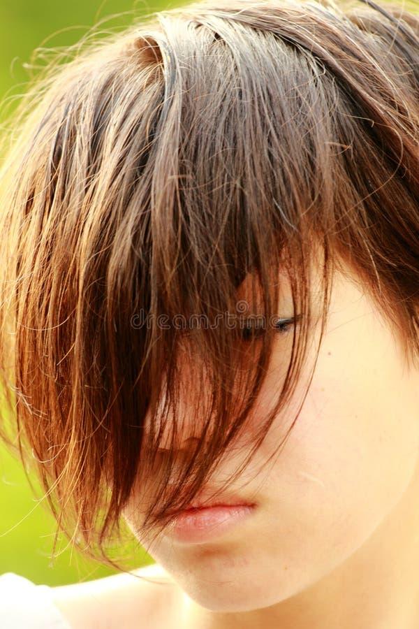 Портрет огорченного корейца, стренги волос покрывает сторону стоковая фотография