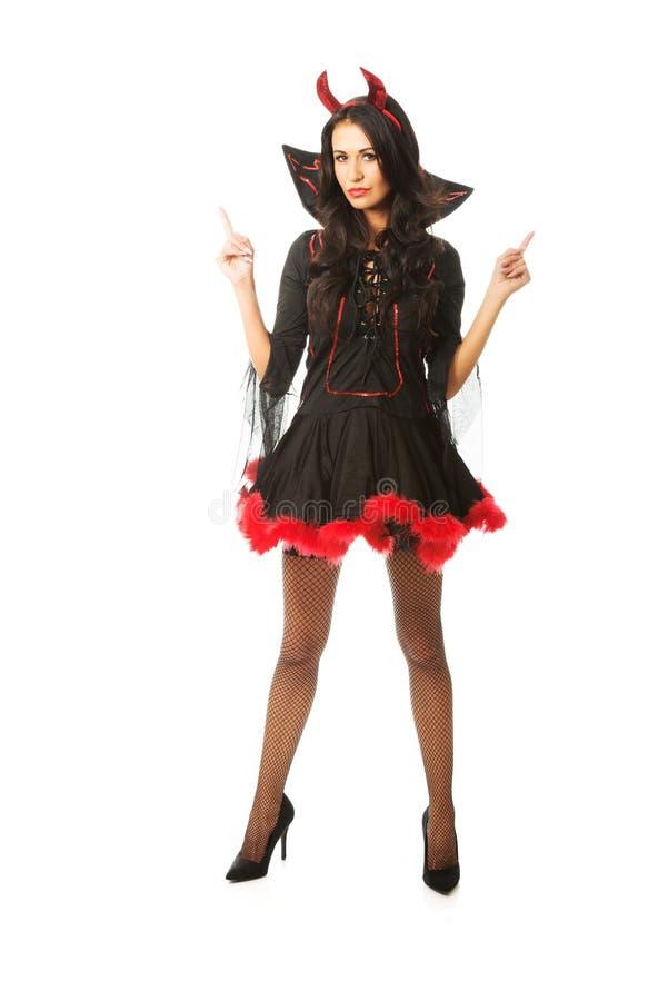 Портрет одежд дьявола женщины нося указывая вверх с обеими руками стоковые фото