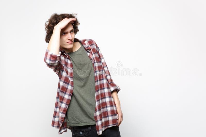 Портрет озадаченного молодого человека в случайных одеждах держит руку на лбе выглядя далеким расстоянием изолированный на белизн стоковые фотографии rf